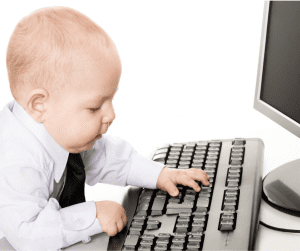 baby in shirt and tie sitting at computer keyboard to emphasise the importance of being business-like when feeding our babies